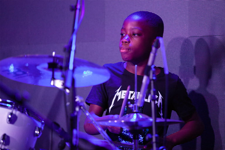 Photograph of a young drummer on stage at an MLC Nottingham performance